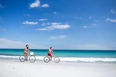 Счастливые пары идя на езду велосипеда Стоковое Фото