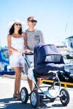 Счастливые пары идя с младенцем outdoors стоковые фото