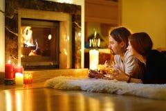 Счастливые пары камином на рождестве Стоковая Фотография
