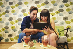Счастливые пары наблюдая социальные средства массовой информации в тетради на баре стоковые фотографии rf