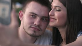 Счастливые пары на праздниках принимая selfie пока сидящ на таблице вне кафа видеоматериал
