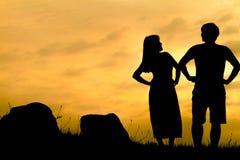 Счастливые пары на утесе захода солнца - силуэте Стоковая Фотография
