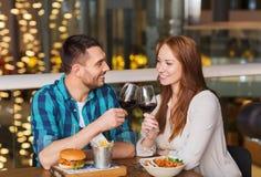 Счастливые пары обедая и вино питья на ресторане Стоковые Фото