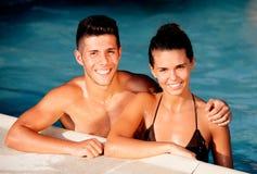 Счастливые пары ослабляя в бассейне Стоковые Фото