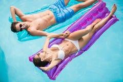 Счастливые пары ослабляя на раздувном сплотке Стоковое фото RF