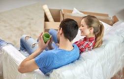 Счастливые пары ослабляя на софе в новом доме Стоковое фото RF