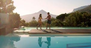 Счастливые пары перескакивая в открытый бассейн акции видеоматериалы