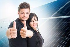 Счастливые пары показывая как на задняя часть панели солнечной энергии фотовольтайческая Стоковые Фотографии RF