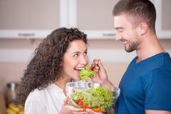 Счастливые пары подготавливая и есть салат в кухне стоковое изображение