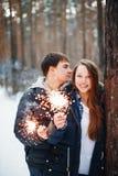 Счастливые пары празднуя рождество в лесе Стоковое Изображение