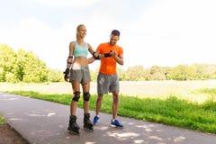 Счастливые пары при коньки ролика ехать outdoors стоковое изображение rf