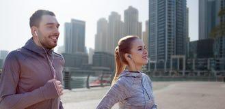 Счастливые пары при наушники бежать в городе Стоковое фото RF