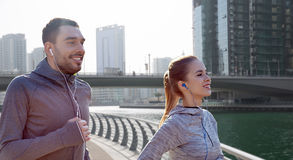 Счастливые пары при наушники бежать в городе Стоковая Фотография RF
