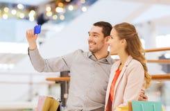 Счастливые пары при smartphone принимая selfie в моле Стоковые Изображения
