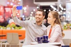 Счастливые пары при smartphone принимая selfie в моле Стоковое Изображение