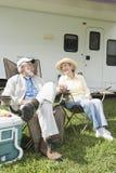 Счастливые пары сидя вне дома RV Стоковая Фотография RF