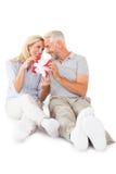 Счастливые пары сидя и держа настоящий момент Стоковые Изображения