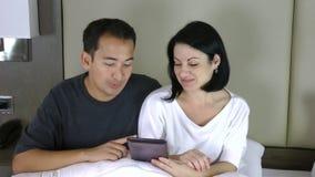 Счастливые пары сидя на кровати и смотря ПК таблетки имея конференцию