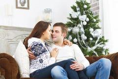Счастливые пары сидя на софе рождественской елкой Стоковые Изображения