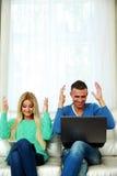 Счастливые пары сидя на софе Стоковое Изображение