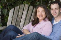 Счастливые пары сидя на стенде снаружи Стоковая Фотография