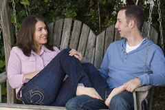 Счастливые пары сидя на стенде снаружи Стоковые Фото