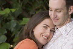 Счастливые пары сидя на стенде снаружи Стоковая Фотография RF