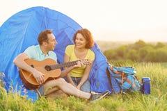 Счастливые пары сидя около шатра с гитарой Стоковая Фотография