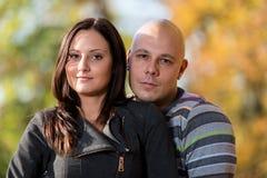 Счастливые пары сидя совместно в древесинах во время осени Стоковые Изображения