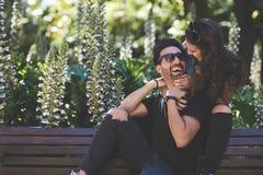 Счастливые пары сидя совместно на смеяться над стенда Стоковое фото RF
