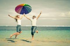 Счастливые пары скача на пляж Стоковая Фотография RF