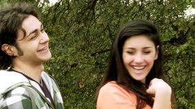 Счастливые пары смеясь над имеющ потеху в парке видеоматериал