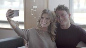 Счастливые пары смотря на мобильном телефоне и смеясь над в caf акции видеоматериалы