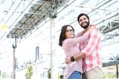 Счастливые пары смотря отсутствующий пока обнимающ внешнее здание Стоковые Фотографии RF