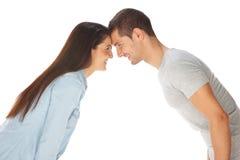 Молодые пары вытаращась на одине другого и усмехаться Стоковые Фотографии RF