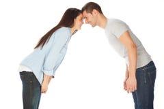 Молодые пары вытаращась на одине другого и усмехаться Стоковые Изображения RF