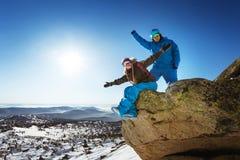 Счастливые пары сноубординга на верхней части гор зимы Стоковая Фотография