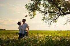 Счастливые пары стоя в поле на заходе солнца стоковое изображение