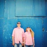 Счастливые пары стоя на голубой предпосылке стены Стоковые Изображения RF