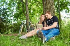 Счастливые пары студентов читают книгу в парке Стоковая Фотография