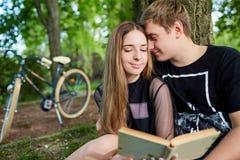 Счастливые пары студентов читают книгу в парке Стоковые Фотографии RF