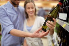 Счастливые пары с бутылкой вина на винном магазине Стоковые Изображения