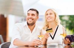 Счастливые пары с карточкой банка и счет на ресторане Стоковое Изображение RF
