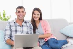 Счастливые пары с компьтер-книжкой на софе Стоковые Изображения RF