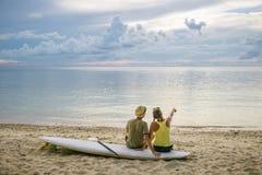 Счастливые пары с доской затвора на пляже на заходе солнца Стоковая Фотография RF