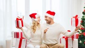 Счастливые пары с подарками и большими пальцами руки рождества вверх Стоковые Фото