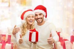 Счастливые пары с подарками и большими пальцами руки рождества вверх Стоковые Изображения RF