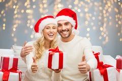 Счастливые пары с подарками и большими пальцами руки рождества вверх Стоковые Фотографии RF