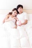 Счастливые пары с розовой копилкой Стоковое фото RF