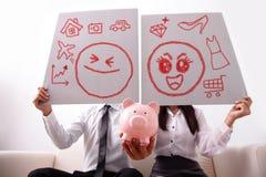 Счастливые пары с розовой копилкой Стоковые Изображения RF